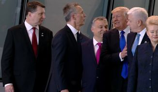 In this image taken from NATO TV, Montenegro Prime Minister Dusko Markovic, second right, appears to be pushed by US President Donald Trump as they were given a tour of NATO's new headquarters after taking part in a group photo, during a NATO summit of heads of state and government in Brussels on Thursday, May 25, 2017. (NATO TV via AP)