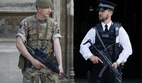An armed soldier and policeman stand guard at Parliament, in London, Thursday, May 25, 2017. Armed troops are guarding vital locations in the country after the official threat level was raised to its highest point following a suicide bombing that killed more than 20 in Manchester. (AP Photo/Kirsty Wigglesworth)