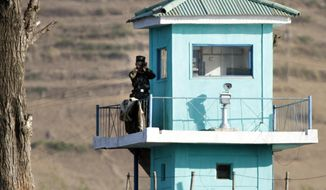 In this Wednesday, May 3, 2017 photo, a North Korean soldier looks through a pair of binoculars as he stands at a guard tower on the border near Chongsu in North Korea's North Pyongan Province, as seen from across the border in Dandong in northeastern China's Liaoning Province. The top U.S. diplomat for East Asia said Friday, May 26, 2017, that Chinese officials have told Washington they have tightened border controls with North Korea as part of U.N. sanctions aimed at halting Pyongyang's nuclear and missile activities. (Chinatopix via AP)