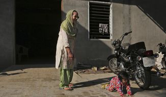 In this Dec. 23, 2016 photo, Manjeet Kaur, left, watches her daughter Gurjeet crawling in the compound of their house in Ellenabad, India. Gurjeet is the child Kaur yearned for desperately, after 40 years of being that thing which a rural Indian woman dreads more than almost anything else - barren. She gave birth at 58 years old, with help from a controversial IVF clinic in this corner of north India that specializes in fertility treatments for women over 50. (AP Photo/Altaf Qadri)