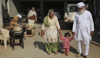 In this Dec. 23, 2016 photo, Manjeet Kaur, left, and her husband Gurdev Singh, right, walk with their daughter Gurjeet Kaur in the compound of their house in Ellenabad, India. Gurjeet is the child Kaur yearned for desperately, after 40 years of being that thing which a rural Indian woman dreads more than almost anything else - barren. She gave birth at 58 years old, with help from a controversial IVF clinic in this corner of north India that specializes in fertility treatments for women over 50. (AP Photo/Altaf Qadri)