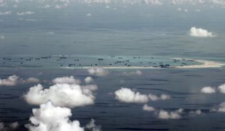 FILE - This May 11, 2015, file photo, shows land reclamation of Mischief Reef in the Spratly Islands by China in the South China Sea. China is protesting a U.S. Navy patrol that brought a guided missile destroyer near a group of manmade islands including Mischief Reef in the South China Sea that are controlled by Beijing. (Ritchie B. Tongo/Pool Photo via AP, File) **FILE**