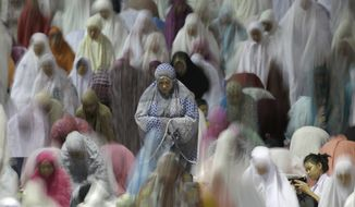 Muslim women perform an evening prayer called 'tarawih' marking the first eve of the holy fasting month of Ramadan, at Istiqlal Mosque in Jakarta, Indonesia, Friday, May 26, 2017. During Ramadan, the holiest month in Islamic calendar, Muslims refrain from eating, drinking, smoking and sex from dawn to dusk. (AP Photo/Tatan Syuflana)