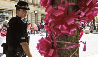 Police patrol past a pink ribbon tribute in central Manchester, England Friday May 26 2017. More than 20 people were killed in an explosion following a Ariana Grande concert at the Manchester Arena late Monday evening. (AP Photo/Rui Vieira)
