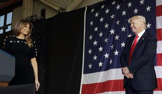 President Donald Trump looks at First lady Melania as he prepares to address U.S. military troops and their families at the Sigonella Naval Air Station, in Sigonella, Italy, Saturday, May 27, 2017. (AP Photo/Luca Bruno)