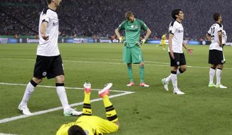 Frankfurt goalkeeper Lukas Hradecky, center, looks down after he played foul against Dortmund's Christian Pulisic, front, during the German soccer cup final match between Borussia Dortmund and Eintracht Frankfurt in Berlin, Germany, Saturday, May 27, 2017. (AP Photo/Michael Sohn)