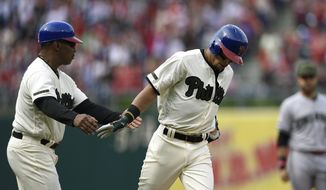 Philadelphia Phillies' Cesar Hernandez, right, is greeted by third base coach Juan Samuel after hitting a solo home run in the first inning of a baseball game against the Cincinnati Redson Saturday, May 27, 2017, in Philadelphia. (AP Photo/Michael Perez)