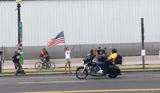 A supporter waves an American Flag as a motorist participating in Rolling Thunder rides by on Constitution Ave. (Laura Kelly/THE WASHINGTON TIMES)
