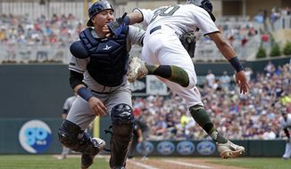 Minnesota Twins' Eddie Rosario,right, tries unsuccessfully to avoid the tag by Tampa Bay Rays catcher Jesus Sucre as he takes to the air trying to score from third in the fourth inning of a baseball game Sunday, May 28, 2017 in Minneapolis. (AP Photo/Jim Mone)