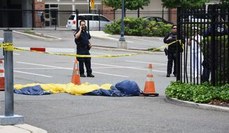 In this Sunday, May 28, 2017 photo, officials surround a U.S. Navy Seal's parachute that landed in a parking lot after the parachutist fell into the Hudson River when his parachute failed to open during a Fleet Week demonstration over the river in Jersey City, N.J. The Navy said the parachutist was pronounced dead at Jersey City Medical Center. (Joe Shine/The Jersey Journal via AP)