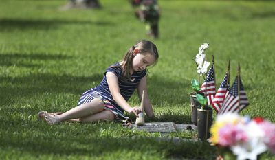 Eight-year-old Piper St. Jean, of Tampa, uses a brush to clean the grave of her grandfather, Henry St. Jean, who served with the United States Air Force during the Korean and Vietnam wars,  at Curlew Hills Memory Gardens on Monday, May 29, 2017, moments after the conclusion of their 31st annual Memorial Day Service in Palm Harbor, Fla. (Douglas R. Clifford/The Tampa Bay Times via AP)