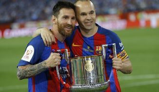 Barcelona's Lionel Messi, left and captain Andres Iniesta pose with the trophy after the Copa del Rey final soccer match between Barcelona and Alaves at the Vicente Calderon stadium in Madrid, Spain, Saturday, May 27, 2017. Barcelona won the match 3-1. (AP Photo/Francisco Seco)