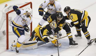 Pittsburgh Penguins' goalie Matt Murray, center, lunges toward the puck as Nashville Predators' Vernon Fiddler, left, and Cody McLeod contend during the first period in Game 1 of the NHL hockey Stanley Cup Final, Monday, May 29, 2017, in Pittsburgh. (AP Photo/Gene J. Puskar)