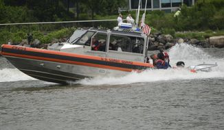 In this Sunday, May 28, 2017 photo, U.S. Coast Guard rescue a U.S. Navy Seal who fell into the Hudson River after his parachute failed to open during a Fleet Week demonstration over the river in Jersey City, N.J. The Navy said the parachutist was pronounced dead at Jersey City Medical Center. (Joe Shine/The Jersey Journal via AP)