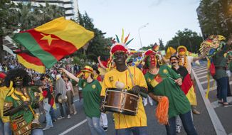 In this photo taken Saturday, May 27, 2017 people carrying a Cameroon flag, take part in a parade in the Black Sea resort of Sochi, Russia. People in blackface wearing African clothing and carrying bananas marched in a government-backed weekend parade in Sochi, a city that will host one of Cameroon's matches at the Confederations Cup. (AP Photo/Artur Lebedev)