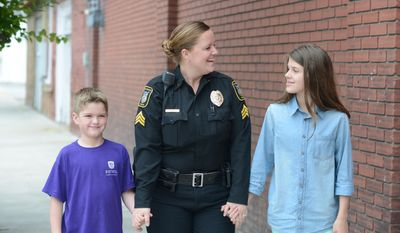 FOR RELEASE SATURDAY, JUNE 3, 2017, AT 12:01 A.M. EDT.- This photo taken May 12, 2017, shows Kinston Police Officer Jessica Stringfield holding hands with her son Cole, left, and daughter Giulianna Russell, right, in Kinston, N.C. (Janet S. Carter /Daily Free Press via AP)