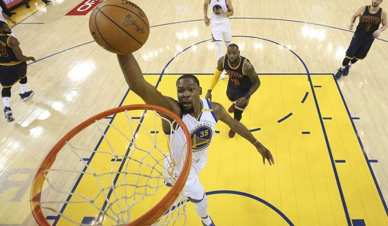 Golden State Warriors forward Kevin Durant (35) dunks in front of Cleveland Cavaliers forward LeBron James during the first half of Game 1 of basketball's NBA Finals in Oakland, Calif., Thursday, June 1, 2017. (Ezra Shaw/Pool Photo via AP)
