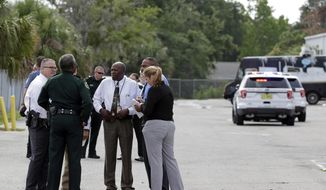 Authorities confer near the scene of a shooting where they said there were multiple fatalities in an industrial area near Orlando, Fla., Monday, June 5, 2017. The Orange County Sheriff's Office said on its official Twitter account that the situation has been contained. (AP Photo/John Raoux)