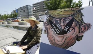 A South Korean protester sits next to a poster with an illustration of U.S. President Donald Trump to oppose a plan to deploy an advanced U.S. missile defense system called Terminal High-Altitude Area Defense, or THAAD, near the U.S. Embassy in Seoul Monday, June 5, 2017. South Korea's presidential office says a senior defense official has been suspended for deliberately failing to report the arrival of several more launchers for a contentious U.S. missile defense system meant to deal with North Korean threats. (AP Photo/Ahn Young-joon)