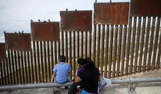 FILE - In this March 2, 2016 file photo, a family looks towards metal bars marking the U.S. border where it meets the Pacific Ocean, in Tijuana, Mexico.  (AP Photo/Gregory Bull, File)