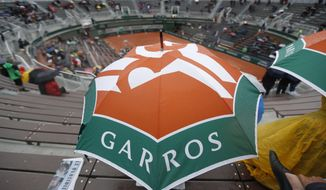 Spectators take cover under umbrellas as third round matches were suspended because of rain showers at the French Open tennis tournament at the Roland Garros stadium, in Paris, France. Saturday, June 3, 2017. (AP Photo/Petr David Josek)