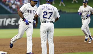 Texas Rangers third base coach Tony Beasley (27) congratulates Adrian Beltre, left, and waits on Joey Gallo, right rear, as the duo scored on a Gallor two-run home run in the third inning of interleague baseball game against the New York Mets on Tuesday, June 6, 2017, in Arlington, Texas. The shot came off a pitch from Mets starter Jacob deGrom. (AP Photo/Tony Gutierrez)