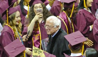 Vermont Sen. Bernie Sanders walks between graduates as he arrives for the Brooklyn College commencement ceremony, Tuesday, May 30, 2017, in New York. The former Democratic presidential candidate, who hails from Brooklyn and attended the school for a year, urged graduates to stand together and not let demagogues divide the country. (AP Photo/Bebeto Matthews)