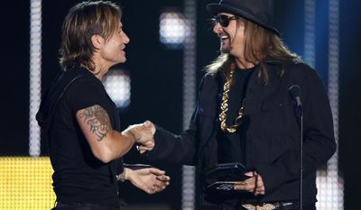 Kid Rock, right, presents the award for video of the year to Keith Urban at the CMT Music Awards at Music City Center on Wednesday, June 7, 2017, in Nashville, Tenn. (Photo by Wade Payne/Invision/AP)