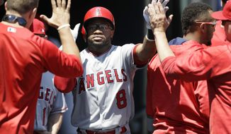 Los Angeles Angels' Eric Young Jr. is greeted in the dugout after scoring in the fifth inning of a baseball game against the Detroit Tigers, Thursday, June 8, 2017, in Detroit. (AP Photo/Carlos Osorio)