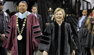 Hillary Clinton, accompanied by Dr. Rudolph Crew, president of Medgar Evers College, arrive for commencement at Barclay's Center, in the Brooklyn borough of New York, Thursday, June 8, 2017. (AP Photo/Richard Drew)
