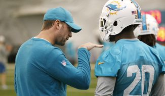Miami Dolphins head coach Adam Gase, left, talks to safety Reshad Jones (20) during an NFL organized team activities football practice, Thursday, June 8, 2017, at the team's training facility in Davie, Fla. (AP Photo/Wilfredo Lee)