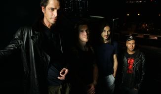 """FILE - In this May 1, 2005, file photo, Audioslave band members Chris Cornell, left to right, Tim Commerford, Brad Wilk and Tom Morello pose before the start of their performance at the 9:30 Club in Washington, D.C. Cornell's former Audioslave bandmates paid tribute to the late singer by performing Audioslave's """"Like a Stone"""" with a spotlight trained on an empty microphone on June 7, 2017, during a show in Berlin. (AP Photo/Manuel Balce Ceneta, File)"""