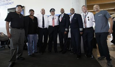 Southwest Airlines captain Louis Freeman, fourth from left, poses for photos with current and retired Southwest pilots before boarding a jet to fly his last flight for Southwest before his retirement in Dallas, Thursday, June 8, 2017. Freeman was the first African-American to become a chief pilot at a major U.S. airline and is retiring after a 36-year career that saw big changes in aviation. His most memorable flight carried the body of civil rights icon Rosa Parks. (AP Photo/LM Otero)