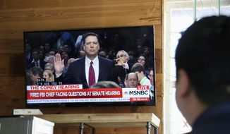 A patron at the Axelrad bar in Houston watches a television as former FBI director James Comey is sworn in before he testified at a U.S. Senate Intelligence Committee hearing on June 8 2017. (AP Photo/John L. Mone)