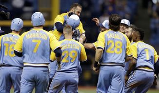 Tampa Bay Rays' Evan Longoria is mobbed by teammates after hitting a walkoff RBI-single off Oakland Athletics relief pitcher Liam Hendriks during the 10th inning of the first game of a scheduled baseball doubleheader Saturday, June 10, 2017, in St. Petersburg, Fla. Rays' Peter Bourjos scored. (AP Photo/Chris O'Meara)