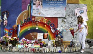 Pulse nightclub owner Barbara Poma tends to the memorial in front of her club Saturday, June 10, 2017, in Orlando, Fla. Many events are being held across central Florida to commemorate the one-year anniversary of the June 12, 2016 massacre at the nightclub that left 49 people dead. (Joe Burbank/Orlando Sentinel via AP)