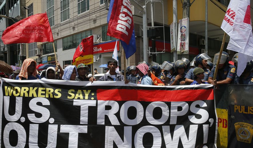 Protesters are blocked by police as they attempt to march closer to the U.S. Embassy to denounce the U.S. military's role in the ongoing battle between Government forces and Muslim militants who laid siege to Marawi city in southern Philippines for three weeks now Monday, June 12, 2017 in Manila, Philippines. The protesters also denounced President Rodrigo Duterte's declaration of Martial Law in the whole region of Mindanao in southern Philippines.(AP Photo/Bullit Marquez)