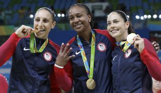 FILE - In this Aug. 20, 2016, file photo, United States' Diana Taurasi, left, Tamika Catchings, center, and Sue Bird, right, celebrate with their gold medals after their win in a women's basketball game against Spain at the 2016 Summer Olympics in Rio de Janeiro, Brazil. Taurasi and Bird, who won their fourth straight Olympic gold medals in Rio, are leaving the door open to continuing their U.S. careers. (AP Photo/Eric Gay, File)