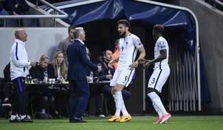 France's Olivier Giroud, centre, celebrates scoring the opening goal with coach Didier Deschamps, left, and teammate Benjamin Mendy during the World Cup 2018 group A qualifying soccer match between Sweden and France Friday June 9, 2017 at the Friends Arena in Solna, Stockholm. (Marcus Eriksson/TT via AP)