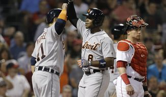 Detroit Tigers' Justin Upton (8) celebrates with Victor Martinez (41) as Boston Red Sox's Christian Vazquez, right, stands nearby after Upton hit a grand slam in the fifth inning of a baseball game, Sunday, June 11, 2017, in Boston. (AP Photo/Steven Senne)