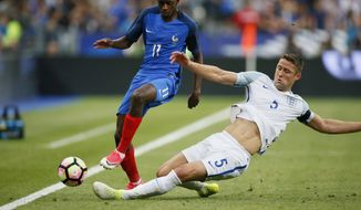 France's Ousmane Dembele, left, challenges for the ball with England's Gary Cahill during a friendly soccer match between France and England at the Stade de France in Saint Denis, north of Paris, France, Tuesday, June 13, 2017. (AP Photo/Francois Mori)