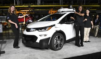 General Motors employees Kayla Green, left, and Crystal Caddell show off a self-driving Chevrolet Bolt EV, one of the cars in the company's autonomous vehicle development program, Tuesday, June 13, 2017, at GM's Orion Assembly in Lake Orion, Mich. The car is one of 130 the company has built at the factory in suburban Detroit, making it among the first automakers to mass produce self-driving vehicles. (Jose Juarez/Detroit News via AP)