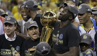 Golden State Warriors forward Draymond Green (23) holds the Larry O'Brien NBA Championship Trophy after Game 5 of basketball's NBA Finals against the Cleveland Cavaliers in Oakland, Calif., Monday, June 12, 2017. The Warriors won 129-120 to win the NBA championship. (AP Photo/Marcio Jose Sanchez)