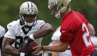 Newly signed New Orleans Saints quarterback Ryan Nassib (2) hands off to running back Adrian Peterson (28) runs through drills during NFL football practice in Metairie, La., Tuesday, June 13, 2017. (AP Photo/Gerald Herbert)
