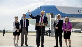 President Donald Trump, accompanied by Michael and Tammy Kushman, left, and Robert and Sarah Stoll, right, speaks in front of Air Force One about healthcare, Tuesday, June 23, 2017, at General Mitchell International Airport in Milwaukee, Wis. (AP Photo/Andrew Harnik)