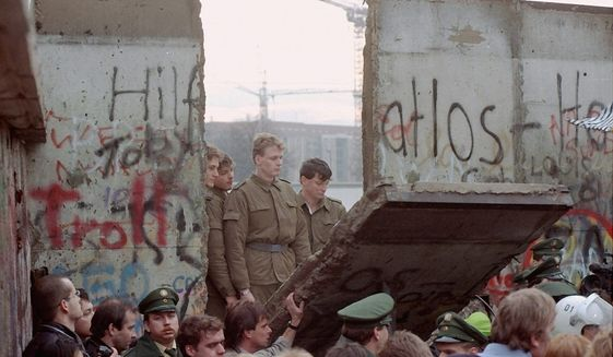 On Nov. 11, 1989, East German border guards are seen through a gap in the Berlin Wall after demonstrators pulled down a segment of the wall at the Brandenburg Gate, Berlin. Associated Press photo