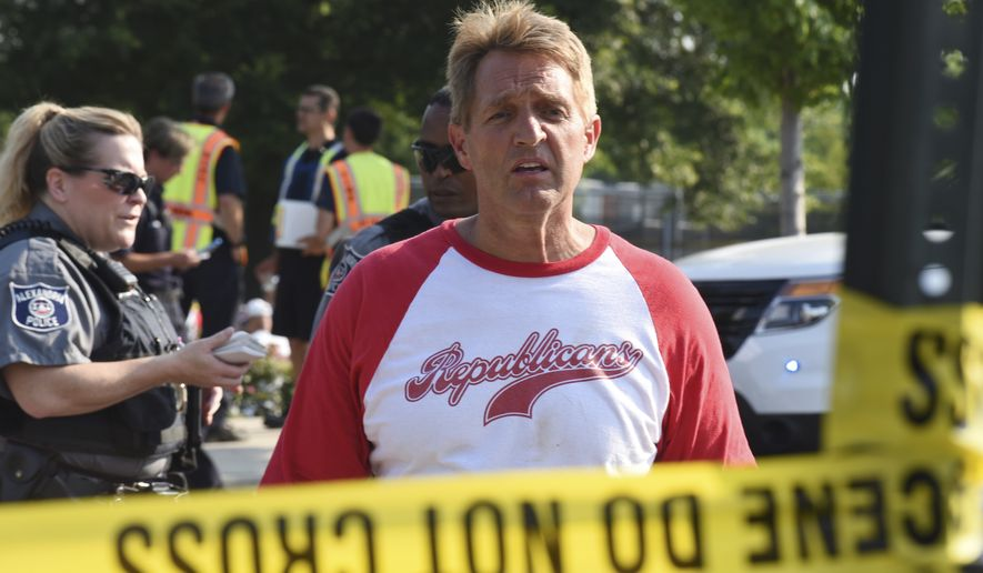 Sen. Jeff Flake, R-Ariz., walks toward media gathered at the scene of a shooting at a baseball field in Alexandria, Va., Wednesday, June 14, 2017, during a Congressional baseball practice where House Majority Whip Steve Scalise of La. was shot. (AP Photo/Kevin S. Vineys)