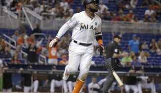 Miami Marlins' Marcell Ozuna watches his solo home run during the fourth inning of the team's baseball game against the Oakland Athletics, Tuesday, June 13, 2017, in Miami. (AP Photo/Lynne Sladky)