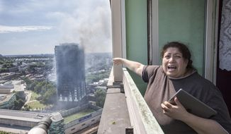 Local resident Georgina stands distraught on her balcony after a fire engulfed the 24-storey Grenfell Tower, in west London, Wednesday June 14, 2017. Fire swept through a high-rise apartment building in west London early Wednesday, killing an unknown number of people with around 50 people being taken to hospital. (Rick Findler/PA via AP)