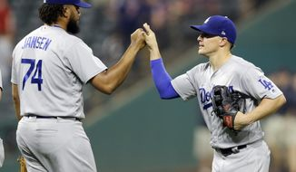 Los Angeles Dodgers' Enrique Hernandez, right, and relief pitcher Kenley Jansen celebrate after the Dodgers defeated the Cleveland Indians 6-4 in a baseball game, Wednesday, June 14, 2017, in Cleveland. (AP Photo/Tony Dejak)
